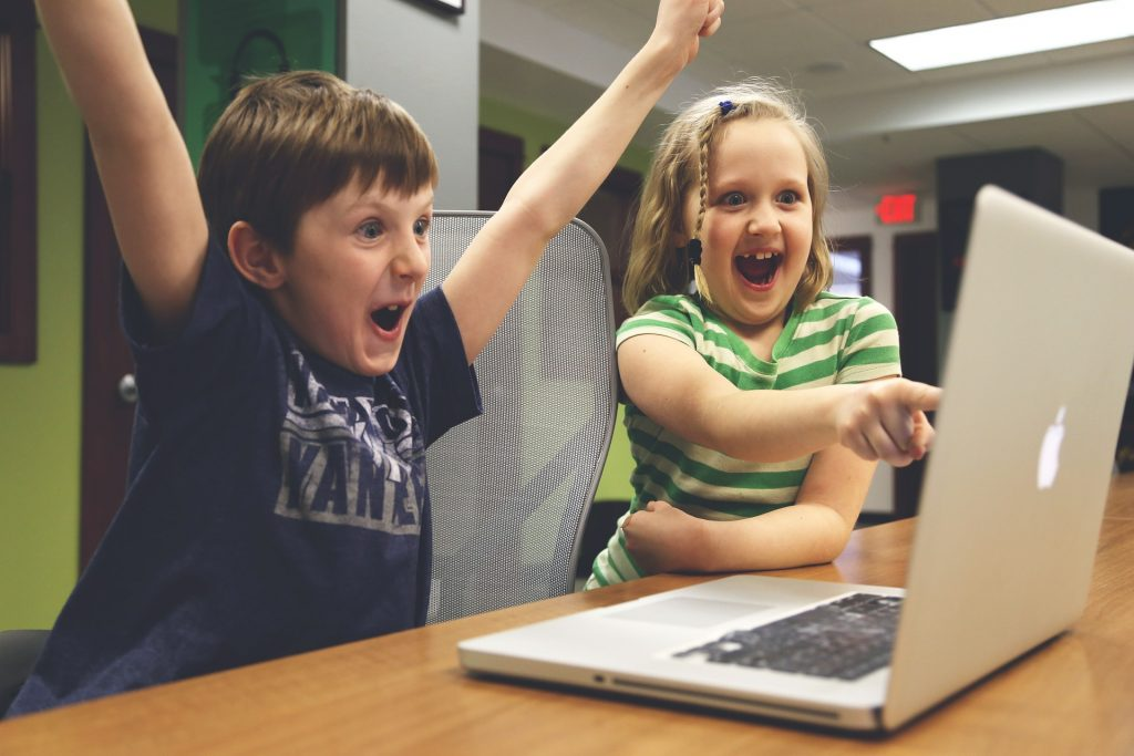 Happy Boy And Girl While Looking At Laptop Screen